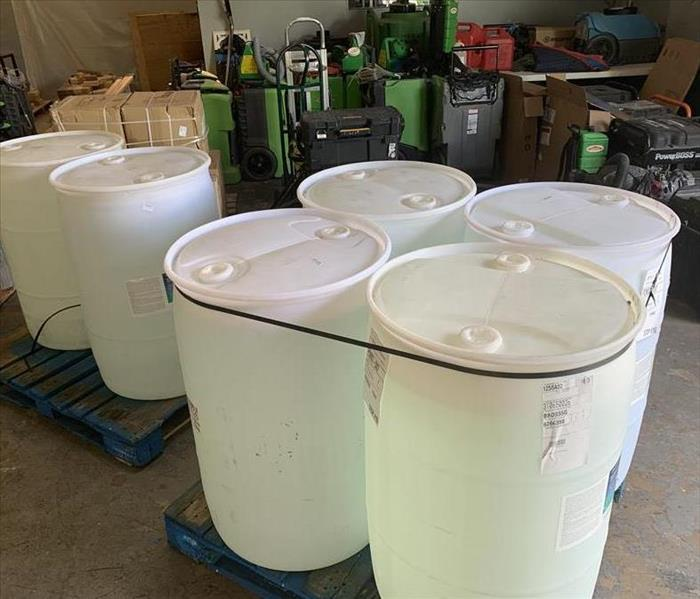Six white barrels in a garage with SERVPRO equipment.