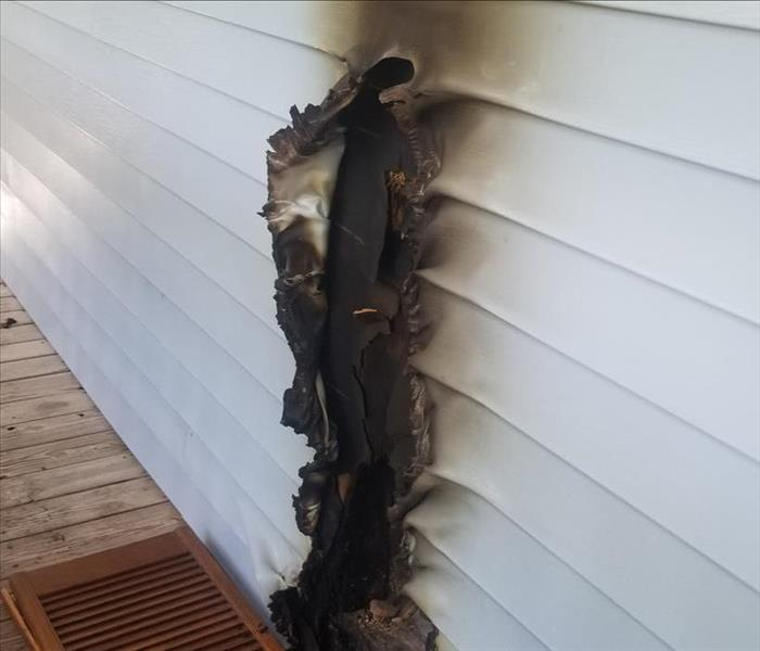 Siding burnt on the side of a home with a wood porch.