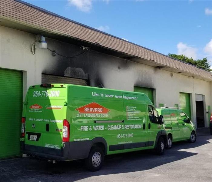 A five car garage building with smoke damage, and SERVPRO vehicles parked in front of the building.