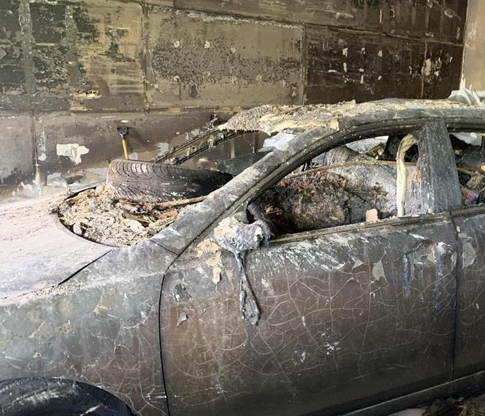 A burnt car with soot and fire damage with a tire on the dash.