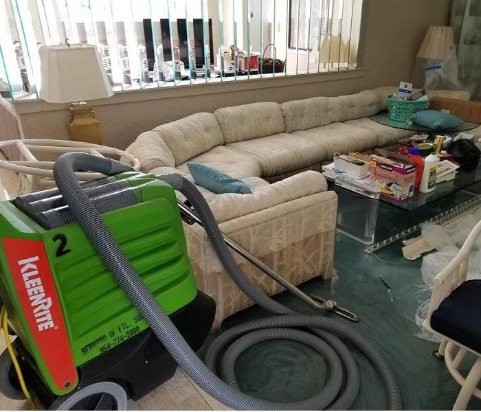 Water on floor of living room.  SERVPRO extraction equipment next to sofa.