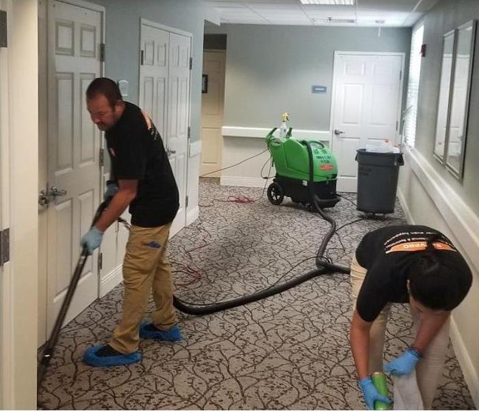 SERVPRO technicians using water extraction equipment to remove water from a commercial properties floor